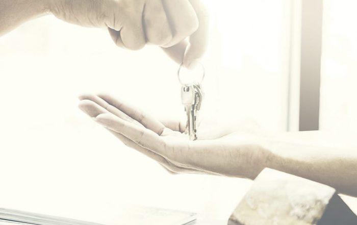 Immobilienmakler gibt Hausschlüssel an Mieter und unterzeichnet Vereinbarung auf Schreibtisch im Büro